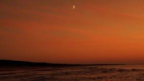 在红色天空的月亮在海 免版税库存照片