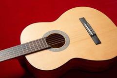 在红色天鹅绒织品,特写镜头对象的声学吉他 库存图片