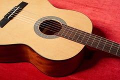 在红色天鹅绒织品,特写镜头对象的声学吉他 库存照片