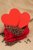 在红色天鹅绒囊的Coffe豆与两红色心脏 库存图片