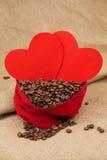 在红色天鹅绒囊的Coffe豆与两红色心脏 免版税库存照片