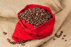 在红色天鹅绒囊的Coffe豆 免版税库存图片