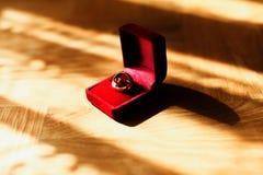 在红色天鹅绒箱子的婚戒在光芒的地板上说谎  图库摄影