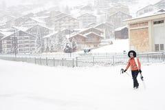 在红色夹克打扮的女孩,镜子滑雪glassed和白色盔甲,运载在她的肩膀的滑雪 免版税库存图片