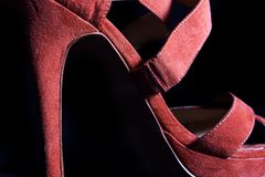 在红色女性高跟鞋鞋子的细节在黑背景 免版税库存照片