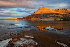 在红色小山的阳光与前景的湖 免版税库存图片