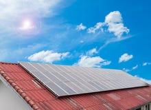在红色屋顶和云彩蓝天的太阳能电池盘区,节能 免版税库存照片