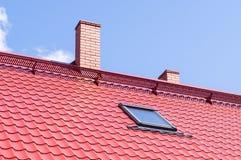 在红色屋顶的砖烟囱有有双重斜坡屋顶的房屋的窗口的 免版税库存图片