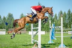 在红色展示套头衫马的车手在跳在背景蓝天的展示的竞技场克服高障碍 库存图片