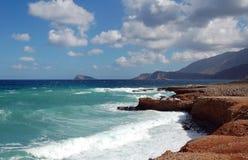 在红色岩石海岸的波浪与山和蓝天 免版税库存图片