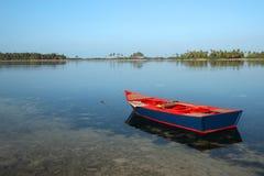 在红色岸附近的小船 免版税库存图片
