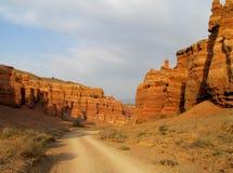 在红色峡谷Charyn (Sharyn)的路在日落 免版税库存图片