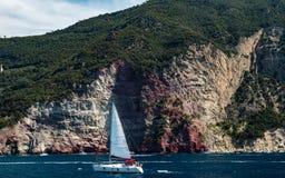 在红色峭壁前面的一点帆船在海岸 库存照片