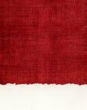 在红色布料的Deckled纸的边缘 库存图片