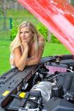 在红色常设妇女附近的美丽的汽车 免版税库存图片