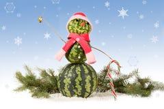 在红色帽子和围巾的西瓜雪人有在蓝色背景和落的雪花的棒棒糖的 免版税库存图片