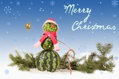 在红色帽子和围巾的西瓜雪人有在蓝色背景和落的雪花的棒棒糖的 免版税图库摄影