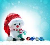 在红色帽子的雪人在多雪的背景 库存照片