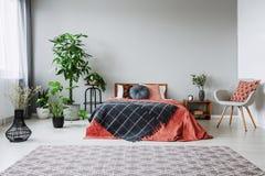 在红色床旁边的扶手椅子与在卧室内部的黑毯子与地毯和植物 免版税库存图片