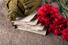 在红色康乃馨花束和一个军用瓶旁边的老信件在被弄皱的纸背景  免版税库存照片