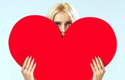 在红色心脏后的逗人喜爱的金发碧眼的女人 库存图片