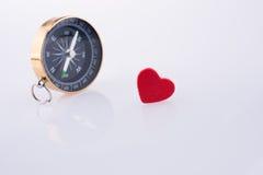 在红色心脏附近的指南针 图库摄影