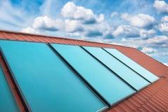 在红色房子屋顶的太阳能电池 免版税图库摄影