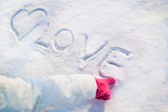 在红色手套的女孩手指画在雪和词爱的心脏 关闭 免版税库存照片
