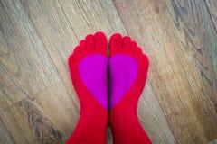 在红色手指的脚殴打形成心脏 库存图片