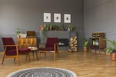 在红色扶手椅子前面的圆的地毯在灰色减速火箭的客厅 图库摄影