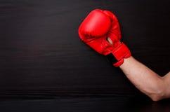 在红色拳击手套的男性手在框架一边的黑背景,文本的地方 免版税库存图片