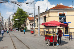 在红色推车附近的卖主用煮沸的玉米,伊斯坦布尔 库存照片