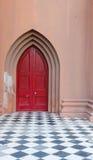在红色教会门的白色门把手 免版税库存图片