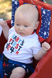 在红色无盖货车的年轻婴儿男孩骑马获得乐趣在7月四的公园 免版税库存照片