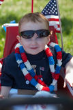 在红色无盖货车的年轻男孩骑马获得乐趣在7月四的公园 库存照片