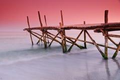 在红色日落下的老木浮船 免版税图库摄影