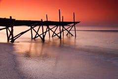在红色日落下的老木浮船 库存图片