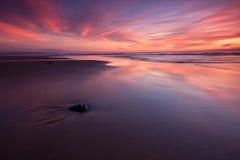 在红色日落的海滩 免版税库存照片