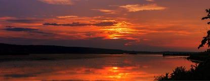 在红色日落的湖 在天空的阴暗五颜六色的云彩, 库存照片