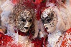 在红色服装的被屏蔽的夫妇在威尼斯狂欢节 库存图片