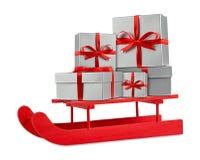 在红色木圣诞老人雪橇的红色银色圣诞节礼物盒 免版税库存照片