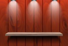 在红色木墙壁上的空的架子 库存图片