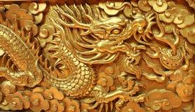 在红色木墙壁上装饰的金黄龙 免版税库存照片