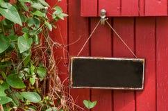 在红色木墙壁前面的金属标志 免版税库存图片