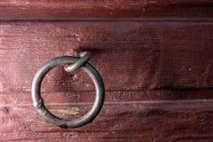 在红色木墙壁的焊接金属链接 免版税图库摄影