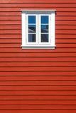 在红色木房子墙壁上的白色木窗口 免版税库存照片