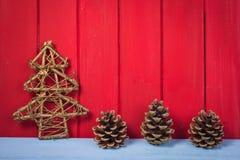 在红色木背景的减速火箭的圣诞树杉木锥体 图库摄影