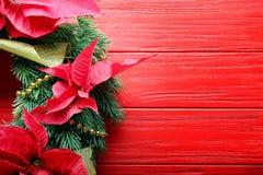在红色木背景的美丽的圣诞节花圈, 库存图片