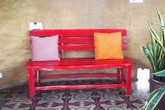 在红色木长凳的枕头 图库摄影
