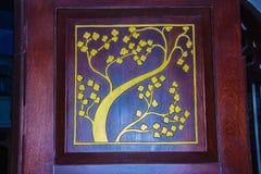 在红色木门事假的被雕刻的金黄花纹花样 免版税库存图片